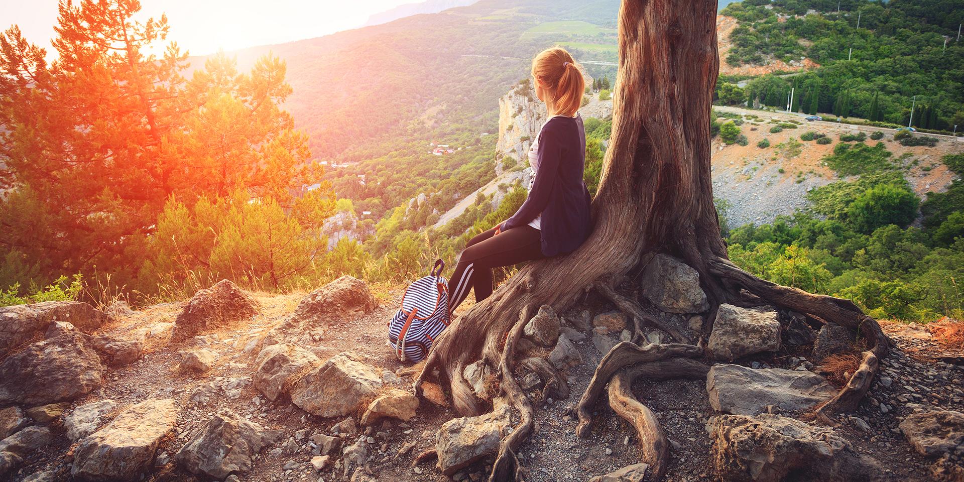 Junge Frau sitzt auf dem Wurzelwerk eines Baumes und blickt in die Weite